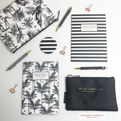 Alice Scott Set of 2 notebooks. One features a black and white stripe with the words 'Never Ending Notes and Lists' and the other is in one of Alice Scott's favourite prints, a tropical palm print with the quote 'Dangerously good ideas' Both feature Gold Foil detailing. Also featured is Alice Scott Set of 3 boxed pens, Alice Scott #nofilter compact mirror and Alice Scott large and small make up bag.