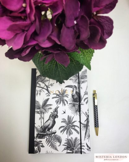 Alice Scott B5 Notebook. Beautifully bound with a fun tropical inspired print featuring palm trees and parrots. Notebook contains 160 lined pages and has a bookmark and elasticated closure.