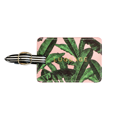 Alice Scott Luggage Tag. Adorned with a pink and banana leaf design it features the word 'Luggage' in gld foil detailing. The luggage tag also has a buckle detail used to attach to your suitcase